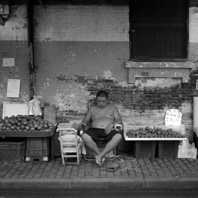Mann verkauft Obst auf der Straße vor heruntergekommener Wand