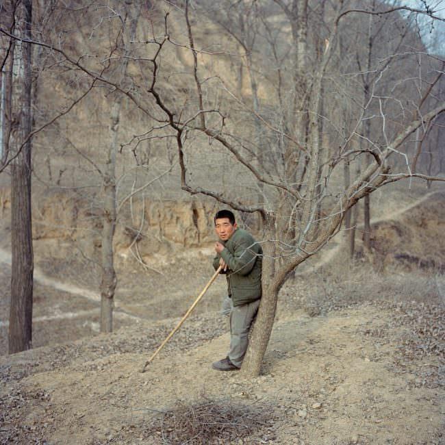 Ein Mann lehnt an einem Baum