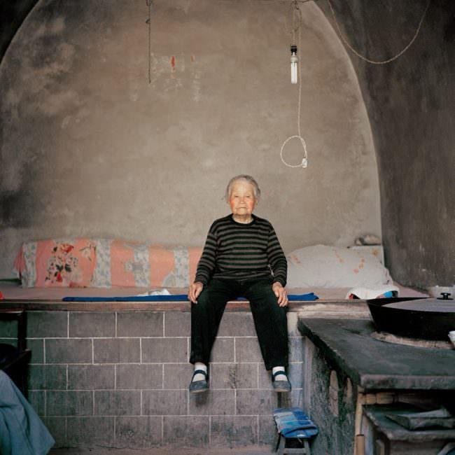 Eine ältere Frau in einem kargen Zimmer