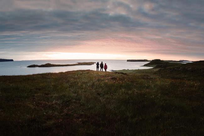 Drei Menschen stehen auf einer Klippe am Meer und sehen in den Sonnenuntergang.