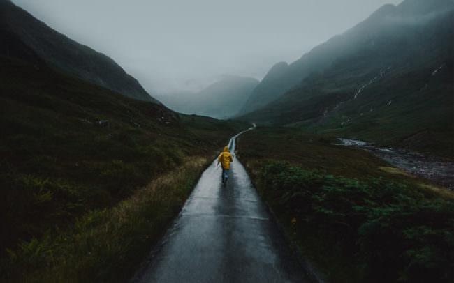 Mann in gelbem Regenmantel läuft entlang eines Weges zu einem Bergpanorama.