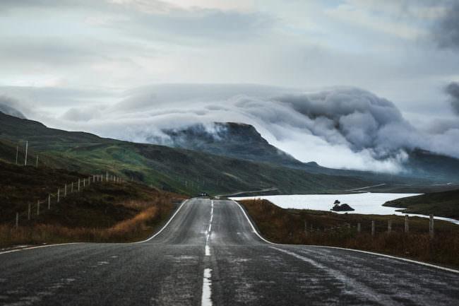 Eine zweispurige Straße führt an einem See vorbei zu einem Bergpanorama in den Wolken.