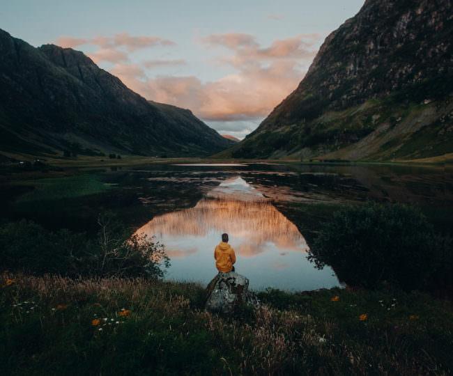 Mann in gelbem Regenmantel sitzt auf einem Stein vor einem See in dem sich Berge bei Sonnenuntergang spiegeln.