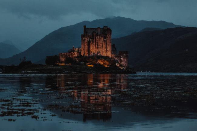 Ein beleuchtetes Schloss bei Nacht vor einem Bergpanorama spiegelt sich in einem See.