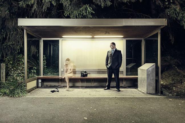 Ein Akt an einer Bushaltestelle mit einer Langzeitbelichtung. Ein Mann im Anzug blickt auf eine nackte Frau