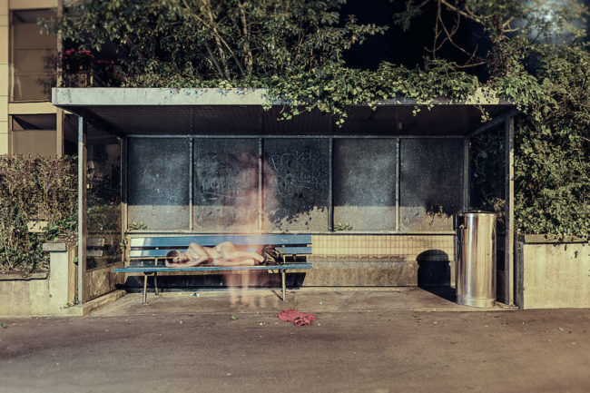 Aktaufnahme einer Frau an einer Bushaltestelle mit Langzeitbelichtung.