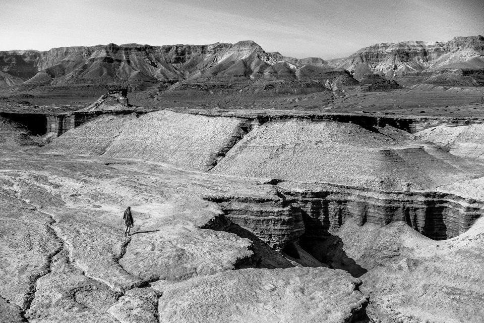 Eine Person läuft durch karge Landschaft