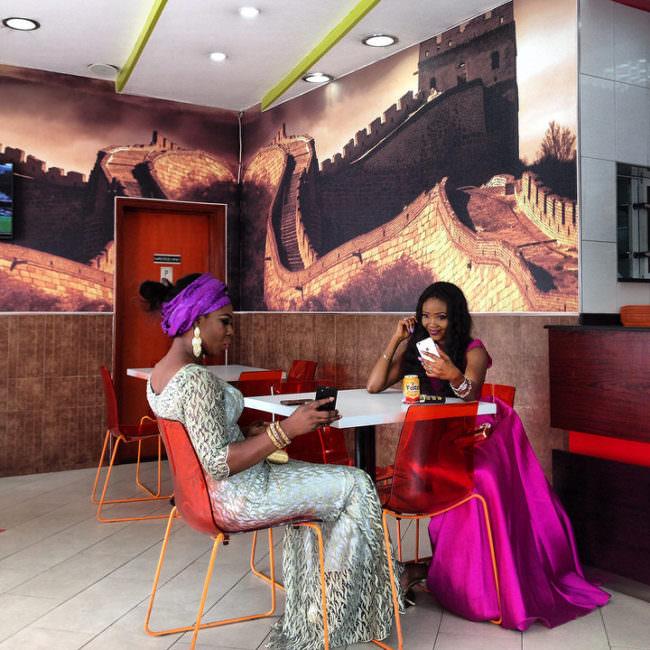 Zwei afrikanische Frauen sitzen in bunten Kleidern in einem Raum am Tisch mit ihren Smartphones in der Hand.