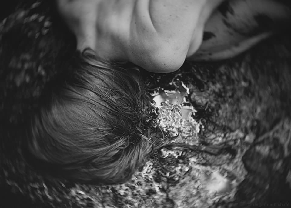 Eine Frau liegt auf nassem Boden