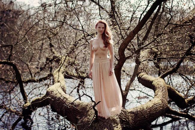 Eine Frau steht auf einem Baum über dem Wasser