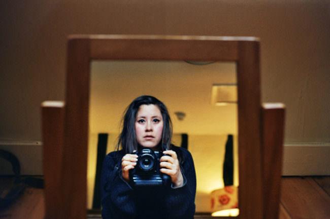 Selbstportrait einer Frau im Spiegel mit Kamera in der Hand