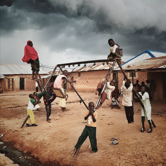 Acht Kinder spielen auf einem Schaukelgerüst unter freiem Himmel.