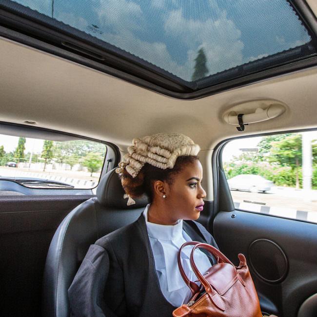 Dunkelhäutige Frau sitzt in einem Auto und hat eine Richterperücke auf und eine Handtasche auf dem Schoß.