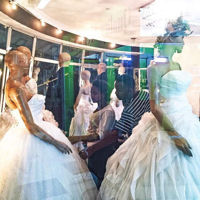 Ein Paar schaut sich Brautkleider in einem Laden an.