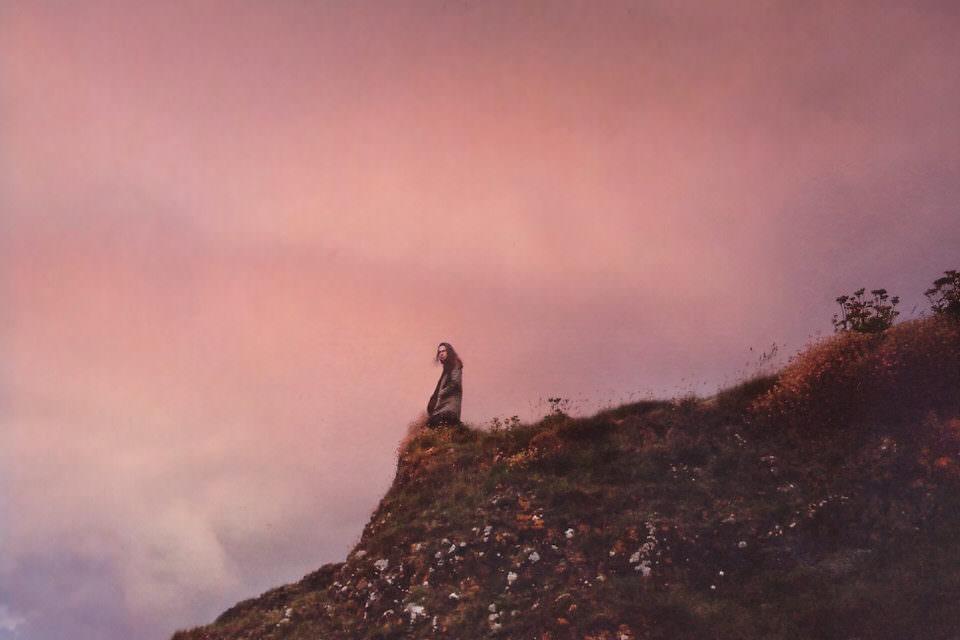 Ein Mann steht an einer grasbewachsenen Klippe.