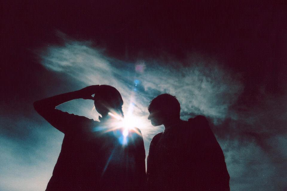 Silhouette von zwei Personen im Gegenlicht vor einem Wolkenhimmel.