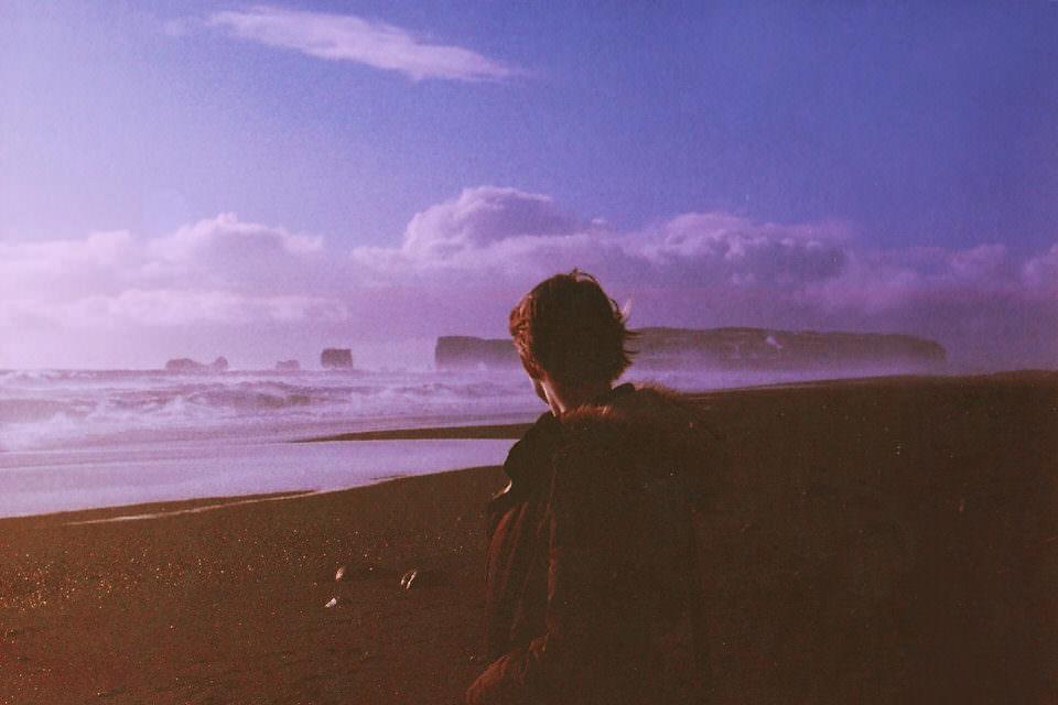 Ein Mann steht an einem Strand und blickt auf Felsen im Meer.