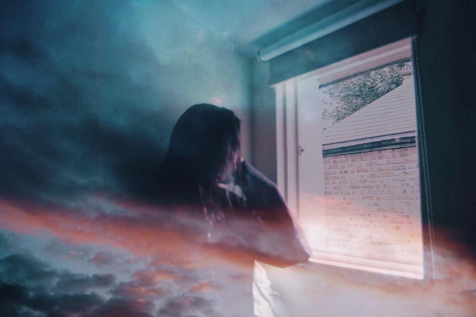 Doppelbelichtung mit einem Wolkenhimmel der über dem Portrait einer Frau liegt, die aus dem Fenster sieht.
