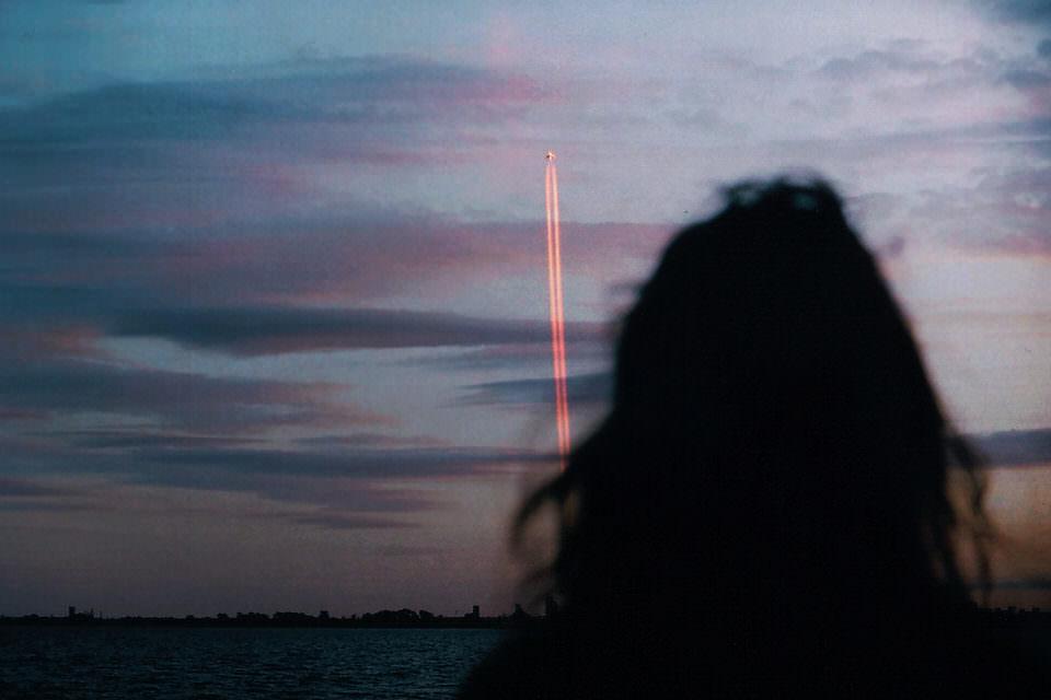 Eine Frau blickt nach oben zu einem Flugzeug mit Kondensstreifen.