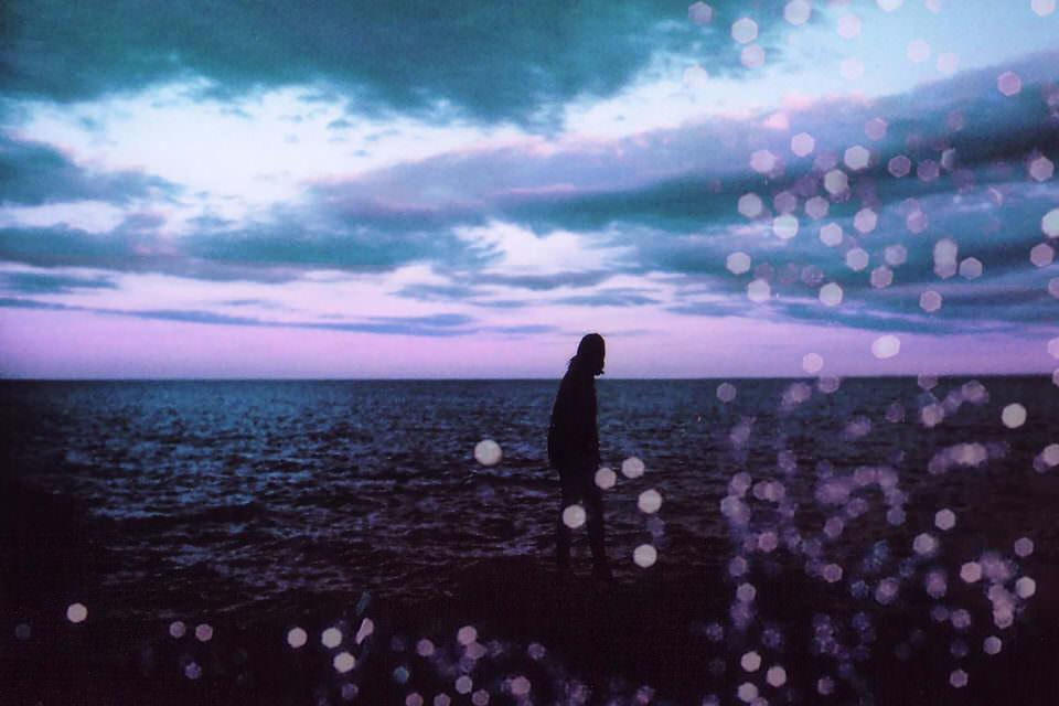 Ein Mann steht auf einem Felsen und blickt auf das Meer.