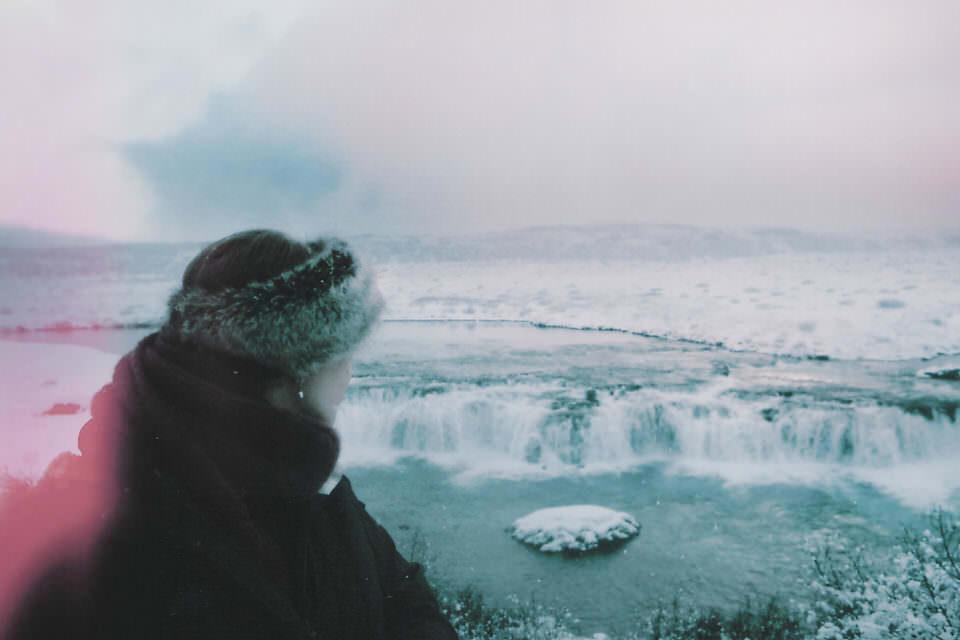 Eine Frau blickt auf einen Wasserfall im Winter.