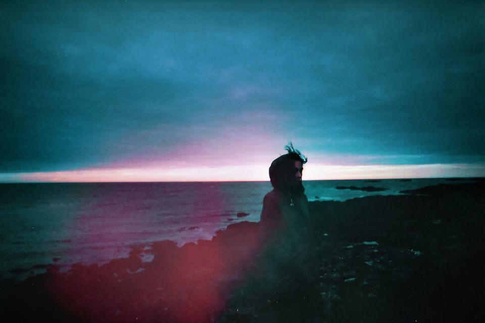 Jemand steht auf einem windigen Felsen am Meer vor einer Wolkenfront.