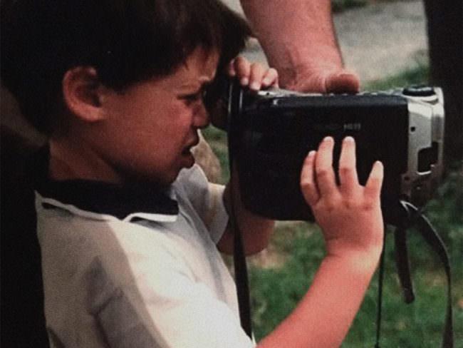 Kind schaut mit Hilfe eines Erwachsenen durch eine Videokamera.