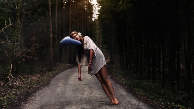 Eine Frau in einem weißen Kleid auf einem Waldweg legt ihren Kopf auf ein Kissen, das in der Luft schwebt.
