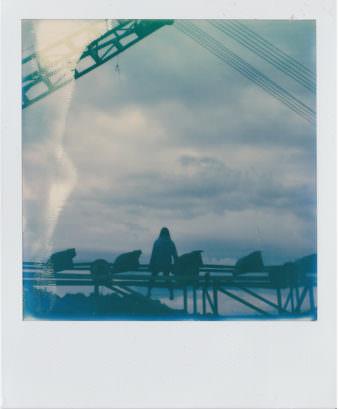 Polaroid, auf dem eine Frau auf einem Gerüst vor einem Wolkenhimmel sitzt.