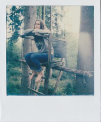 Polaroid einer Frau die auf einem Hochsitz zwischen zwei Bäumen sitzt.