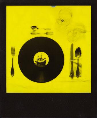Gelbstichiges Poloaroid eines gedeckten Tisches, auf dem statt eines Tellers eine Schallplatte mit dem Bild eines Bootes liegt.