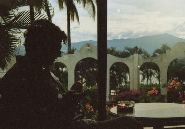 Silhouette eines Mannes mit einer Zigarette in der Hand der auf sein Smartphone blickt und vor einem Blumengarten sitzt.