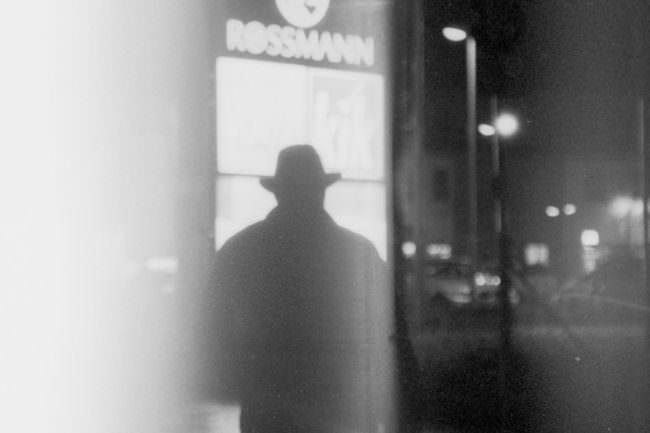Silhouette eines Mannes mit Hut auf einer Straße bei Nacht.