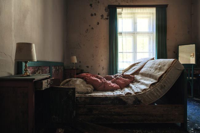 Ein heruntergekommenes Schlafzimmer mit einem Bett und einer Matratze in einem verlassenen Haus.