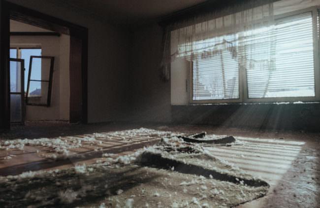 Ein Raum in einem verlassenen Gebäude mit Daunen auf dem Boden. Durch das Fenster dringt Tageslicht in den Raum.