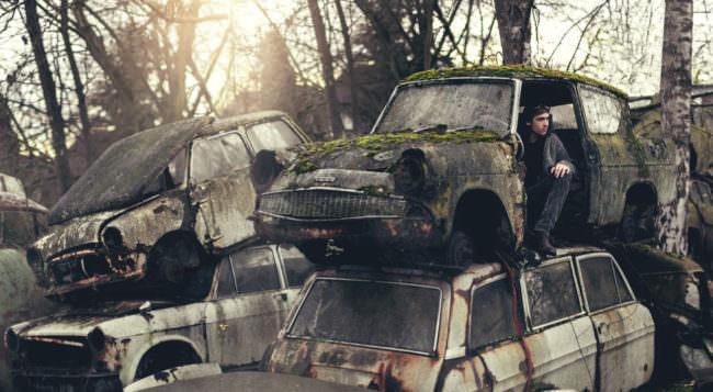 Ein Mann sitzt in der Fahrertür eines heruntergekommenen Autos das auf einem anderen Auto auf einem alten Schrottplatz liegt.