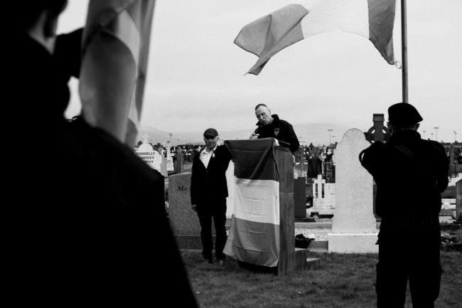 Ein Mann redet an einem Pult mit Flagge
