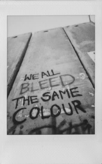 """Auf einer Mauer steht """"We all bleed the same colour"""""""