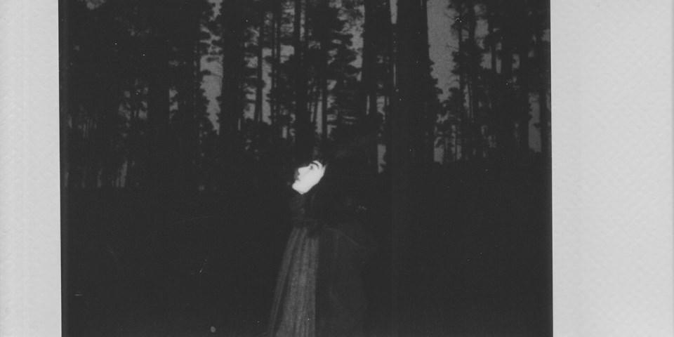 Eine Person steht vor dunklen Bäumen