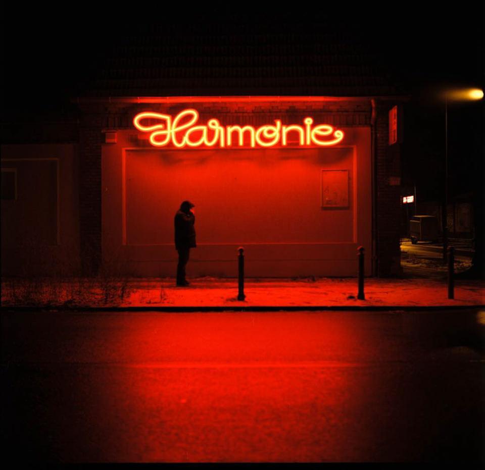 Eine Person steht unter einem roten Neonschriftzug