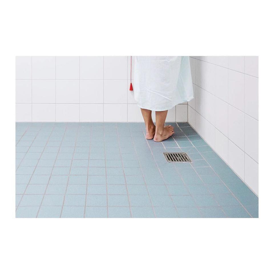 Die Füße einer Person auf gefließtem Boden