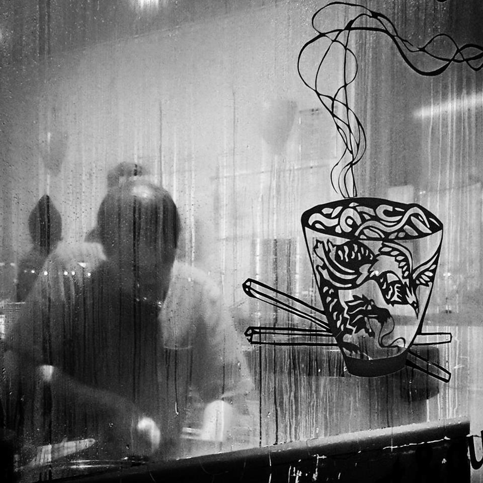 Eine Person hinter einer Scheibe, auf der die Zeichnung einer Suppenschüssel zu sehen ist.