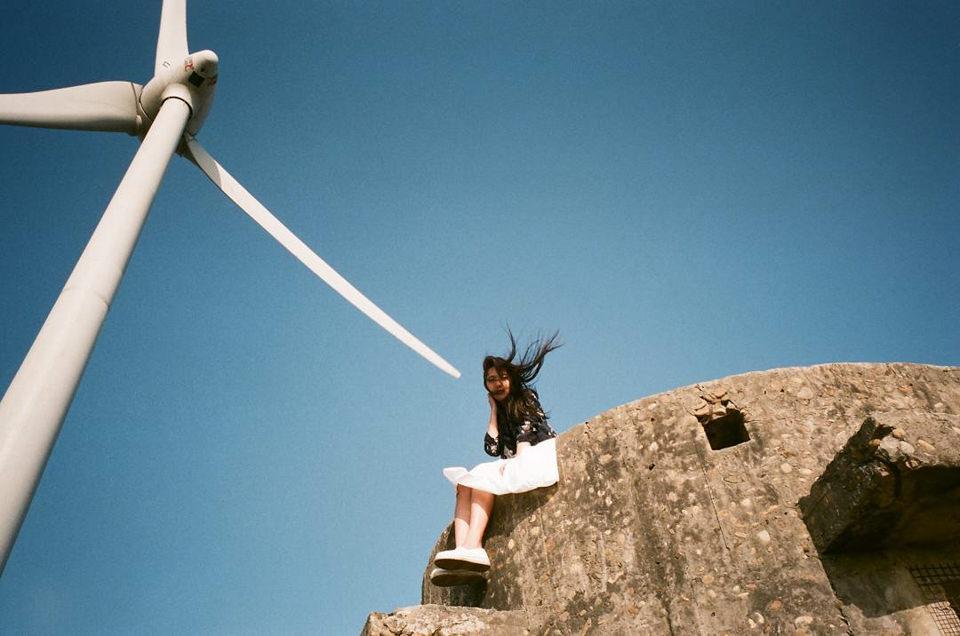 Eine Person sitzt unter einem Windrad auf einer Mauer