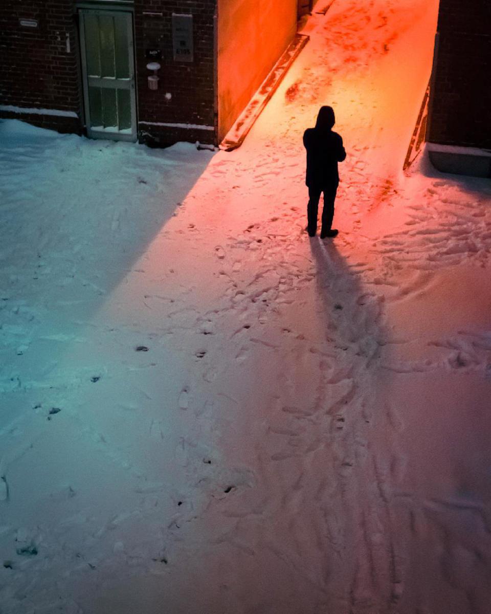 Eine Person steht in einer beleuchteten, verschneiten Straße