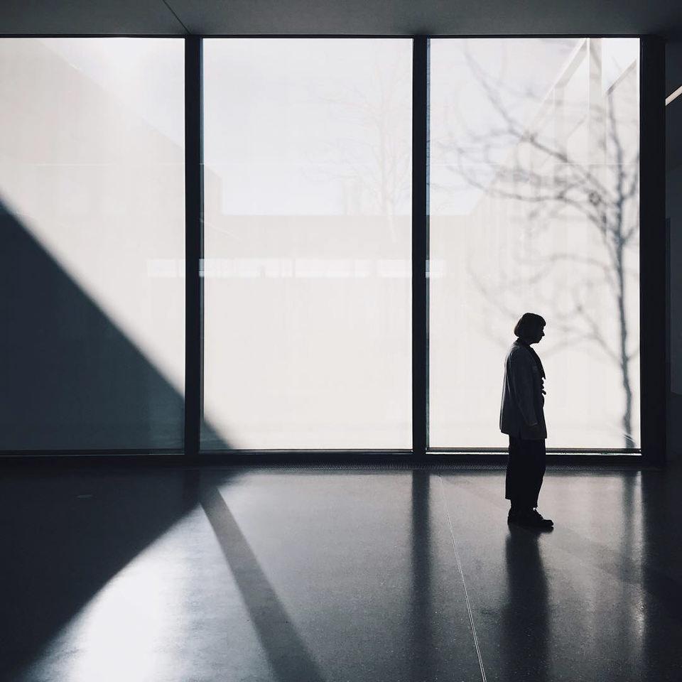 Silhouette einer Person vor großen Fenstern