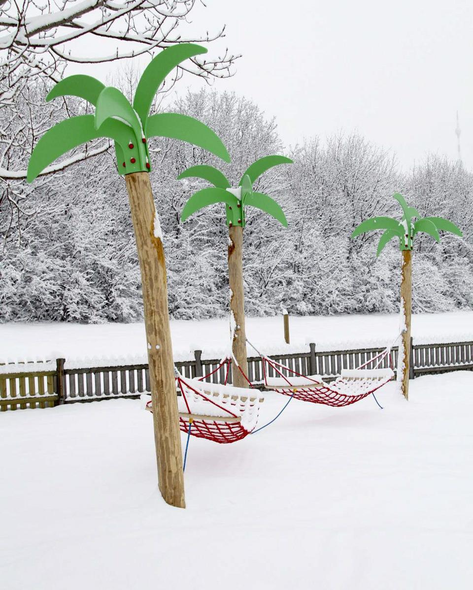 Hängematten hängen künstlichen Palmen in verschneiter Landschaft