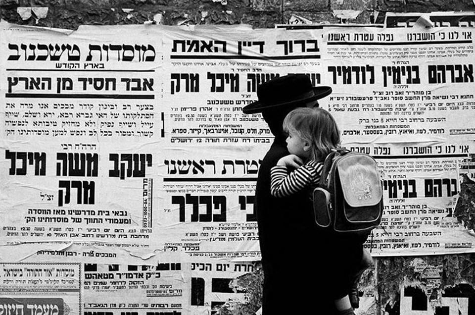 Eine Person trägt ein Kind an einer mit hebräischen Plakaten behangenen Wand vorbei