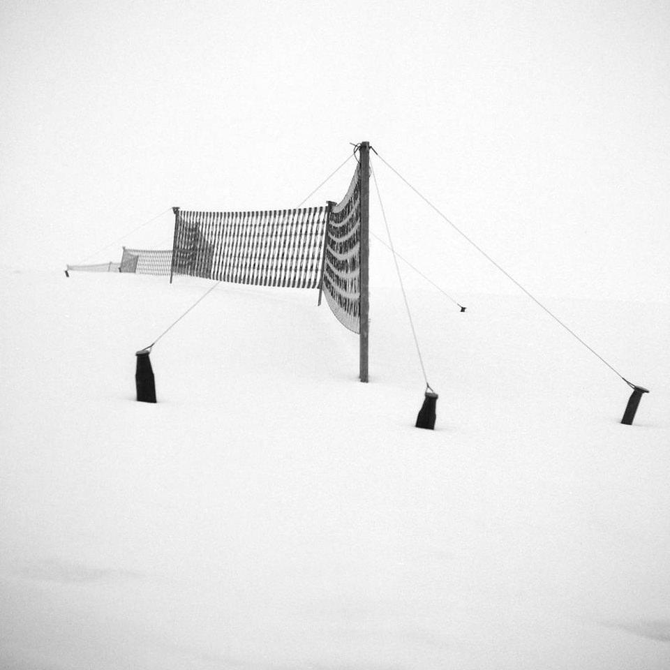 Ein Zaun in verschneiter Landschaft