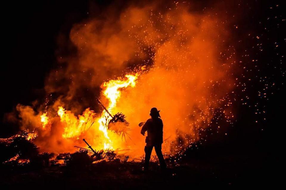 Umrisse einer Person vor Flammen und Rauch