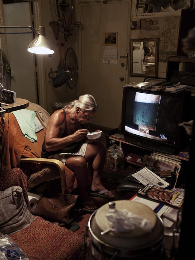 Älterer Herr in einem Innenraum isst aus einer Schale.